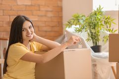 Mujer feliz joven con llave y pertenencia en el nuevo hogar foto de archivo libre de regalías