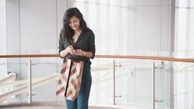 Mujer feliz joven con los bolsos en la alameda