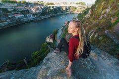 Mujer feliz joven con los dreadlocks rubios que se sientan en un alto acantilado sobre el río Imágenes de archivo libres de regalías
