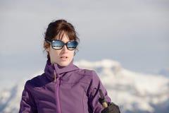 Mujer feliz joven con los polos de esquí en el esquí del invierno Foto de archivo