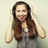 Mujer feliz joven con música que escucha de los auriculares Imágenes de archivo libres de regalías