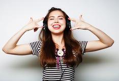 Mujer feliz joven con música que escucha de los auriculares Foto de archivo libre de regalías
