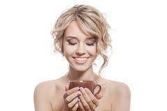 Mujer feliz joven con un café aromático en manos. Aislado foto de archivo libre de regalías