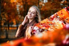 Mujer feliz joven con una bufanda en el viento en el otoño Fotos de archivo