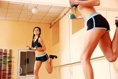 Mujer feliz joven del ajuste que hace ejercicios con los dumbells Fotografía de archivo
