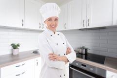 Mujer feliz joven del cocinero en el uniforme que presenta en cocina Imagenes de archivo