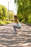 Mujer feliz joven del deporte que hace posiciones en cuclillas con pesas de gimnasia en el parque imágenes de archivo libres de regalías