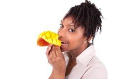 Mujer feliz joven del negro/del afroamericano que come el mango fresco Imagen de archivo