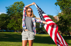 Mujer feliz joven del patriota que sostiene la bandera de Estados Unidos Imágenes de archivo libres de regalías