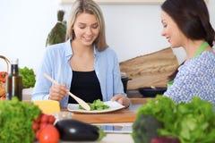 Mujer feliz joven dos que hace cocinar en la cocina Amistad y concepto culinario imagen de archivo