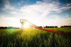 Mujer feliz joven en campo de trigo con la tela Forma de vida del verano Foto de archivo libre de regalías