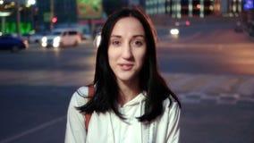 Mujer feliz joven en ciudad en el retrato serio de la cara de la noche en el fondo borroso de los carlights entonado metrajes