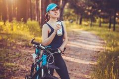 Mujer feliz joven en el agua potable de reclinación de la bici imagen de archivo