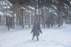 Mujer feliz joven en el bosque en una nevada fuerte Fotografía de archivo