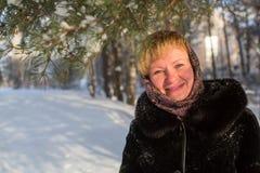 Mujer feliz joven en el invierno en el pueblo ruso nevoso Fotos de archivo libres de regalías