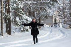 Mujer feliz joven en el invierno en el pueblo ruso nevoso Fotografía de archivo libre de regalías