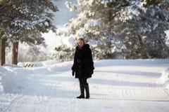 Mujer feliz joven en el invierno en el pueblo ruso nevoso Imagen de archivo