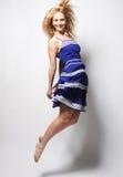 Mujer feliz joven en el salto azul del vestido Fotos de archivo libres de regalías