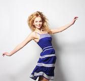 Mujer feliz joven en el salto azul del vestido Imagenes de archivo