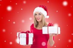 Mujer feliz joven en el sombrero de santa que presenta con las cajas de regalo sobre c roja Foto de archivo
