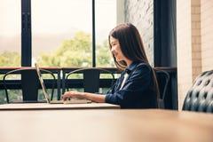 Mujer feliz joven en la ropa casual que trabaja en su ordenador, usted fotografía de archivo libre de regalías