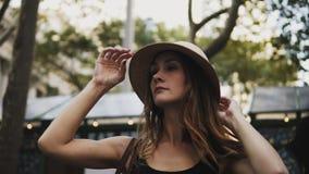 Mujer feliz joven en mercado callejero Exterior derecho de la mujer hermosa y el intentar en los sombreros, sonriendo almacen de video