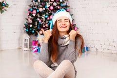 Mujer feliz joven en suéter caliente cerca del árbol del Año Nuevo con prese Imagenes de archivo