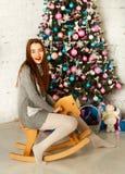 Mujer feliz joven en sweather caliente cerca del árbol del Año Nuevo que sienta o Fotos de archivo libres de regalías