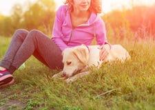 Mujer feliz joven en un prado verde con el perro blanco del perro perdiguero Fotografía de archivo libre de regalías