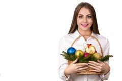 Mujer feliz joven europea hermosa con la piel sana y sonrisa encantadora en la camisa blanca con la cesta de decoraciones de la N Foto de archivo
