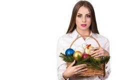 Mujer feliz joven europea hermosa con la piel sana y sonrisa encantadora en la camisa blanca con la cesta de decoraciones de la N Fotografía de archivo
