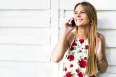 Mujer feliz joven hermosa que sonríe durante una llamada de teléfono Fotos de archivo