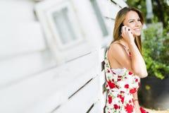 Mujer feliz joven hermosa que sonríe durante una llamada de teléfono Imágenes de archivo libres de regalías