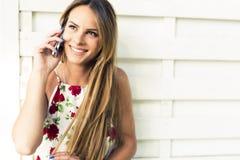 Mujer feliz joven hermosa que sonríe durante una llamada de teléfono Fotografía de archivo