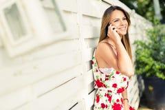 Mujer feliz joven hermosa que sonríe durante una llamada de teléfono Fotografía de archivo libre de regalías