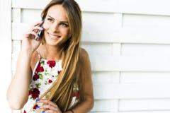 Mujer feliz joven hermosa que sonríe durante una llamada de teléfono Imagenes de archivo