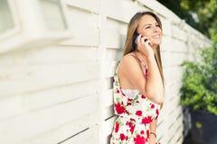 Mujer feliz joven hermosa que sonríe durante una llamada de teléfono Fotos de archivo libres de regalías