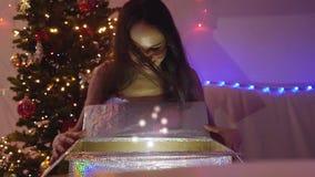 Mujer feliz joven que abre el regalo de Navidad mágico en la cámara lenta La muchacha se sienta al lado de árbol de Navidad en el metrajes