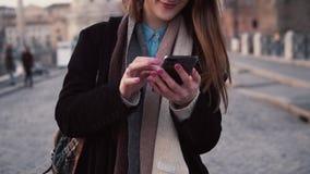 Mujer feliz joven que camina en ciudad y que usa smartphone La muchacha hojea Internet, pasando vacaciones en Roma, Italia almacen de metraje de vídeo