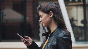 Mujer feliz joven que camina en la calle de la ciudad mientras que usa smartphone Cámara lenta almacen de video
