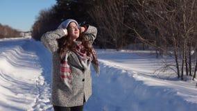 Mujer feliz joven que camina en la calle del invierno metrajes