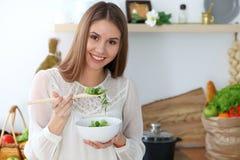 Mujer feliz joven que cocina en la cocina Comida sana, forma de vida y conceptos culinarios La buena mañana comienza con fresco imagen de archivo