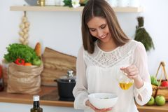 Mujer feliz joven que cocina en la cocina Comida sana, forma de vida y conceptos culinarios La buena mañana comienza con fresco foto de archivo libre de regalías