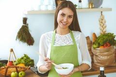 Mujer feliz joven que cocina en la cocina Comida sana, forma de vida y conceptos culinarios La buena ma?ana comienza con fresco fotografía de archivo libre de regalías