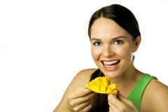 Mujer feliz joven que come el mango sobre blanco Fotos de archivo libres de regalías