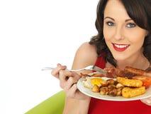 Mujer feliz joven que come un desayuno inglés lleno imagenes de archivo