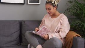 Mujer feliz joven que escribe con la inspiración en cuaderno en el sofá cómodo almacen de metraje de vídeo
