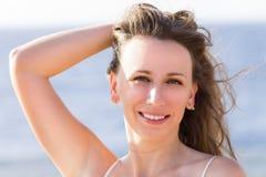 Mujer feliz joven que goza del sol caliente en la playa Imagen de archivo