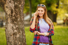 Mujer feliz joven que habla en el teléfono celular en parque de la ciudad del verano Muchacha moderna hermosa en gafas de sol con Fotografía de archivo