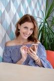 Mujer feliz joven que habla en el teléfono móvil con el amigo mientras que se sienta solamente en el interior moderno de la cafet Foto de archivo